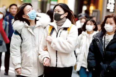 Pedestrians wearing protective masks to help stop the spread of a deadly the coronavirus walk on a street in Tokyo's Ginza area. - AFP