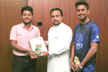 Minister Wimal Weerawansa with undergrads Dulanjana Vithanage and Udam Hettige, when they presented their project report to the Minister.