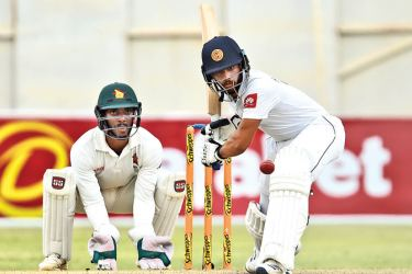 Sri Lanka's Kusal Mendis (R) prepares to play a shot as Zimbabwe's Regis Chakabva (L) looks on during the second Test cricket match at the Harare Sports Club in Harare on Friday. - AFP