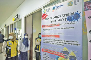 Indonesian health officials stand next to a banner shows information about the SARS-like virus at the Juanda International airport in Sidoarjo, East Java on January 30, 2020.