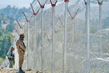 Soldiers keep vigil next to the newly fenced border with Afghanistan.