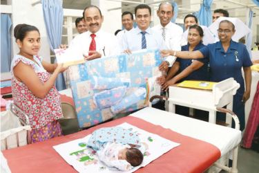 People's Bank Chairman Sujeewa Rajapakse offering a gift to a newborn baby at the Castle Street Hospital, Borella.