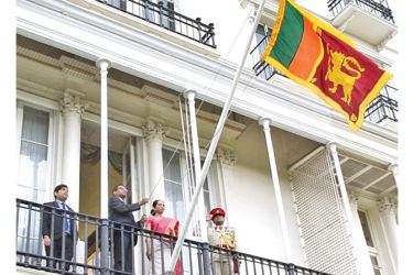 The Acting High Commissioner hoisting the flag.