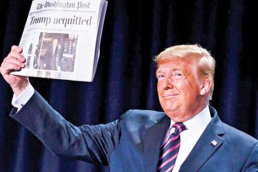 """US President Donald Trump holds up a newspaper with the headline that reads """"ACQUITTED"""" at the 68th annual National Prayer Breakfast, at the Washington Hilton on Thursday."""