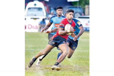 CR and FC winger Janidu Dilshan on his way to score a try with an Air Force Defender making a vain attempt to foil him in their Dialog 'A' Division League Rugby Match played at Longden place yesterday which CR and FC won