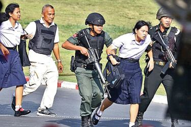 Thai soldiers taking some of the civilians who were trapped in the mall to safety.