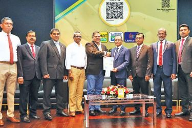 The Bank of Ceylon's CEO/ General Manager Senarath Bandara exchanges signed MoU with Sri Lanka Mobitel (Pvt) ltd CEO Nalin Perera. Officials representing the Bank of Ceylon and Sri Lanka Mobitel are also in the picture.
