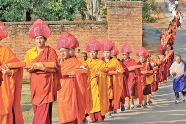 The Bhutanese Buddhist monks walking in procession to the hall to chant Kanjur Pirith yesterday morning.