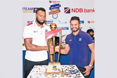 Rival captains Kieron Pollard (West Indies) and Dimuth Karunaratne (Sri Lanka) shake hands in front of the NDB Bank Cup which will be awarded to the winners of the three-match ODI series. Pic by Sudath Malaweera