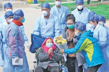 A recovered patient (C in wheelchair), 98, is discharged from Leishenshan Hospital, the makeshift hospital for the COVID-19 coronavirus patients, in Wuhan in China's Hubei province on Sunday. - AFP