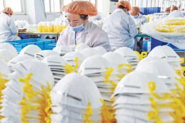 Workers producing face masks at a factory in Handan in China's Hebei Province. - AFP