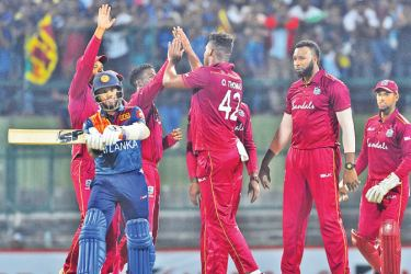 West Indies Oshane Thomas (C) celebrates with his teammates after dismissing Sri Lanka's Kusal Mendis (L) during the first Twenty20 international cricket match of a two-match series between Sri Lanka and West Indies at the Pallekele International Cricket Stadium in Kandy on March 4. AFP