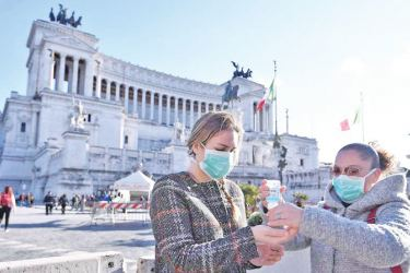 Women wearing face masks disinfect their hands in central Piazza Venezia, in Rome.