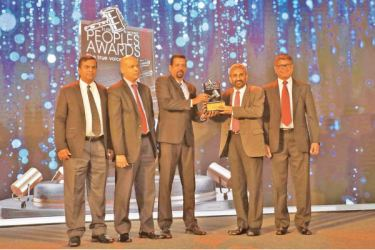 """The Bank's Acting General Manager D.P.K. Gunasekara receiving the """"Peoples Banking Service Provider of the year"""" award (middle). Deputy General Manager, W.N.P. Suranimala, The Bank's Senior Deputy General Manager Human Resource, K.E.D. Sumanasiri, and Chief Marketing Officer Dr. Indunil Liyanage also in the photograph (Left to right)."""