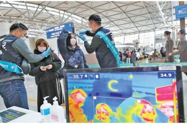 Health officials monitor airline passengers and check  their temperature as they pass a thermal scanner monitor upon arrival.