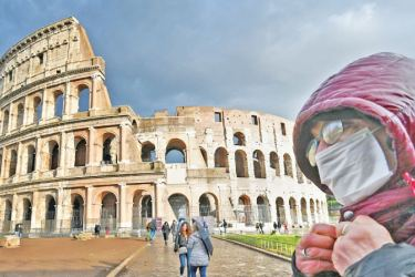 A man wearing a protective mask passes by the Coliseum in Rome on March 7, 2020 amid the COVID-19 fear. - AFP