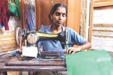Kananathan Reka works on a cloth shopping bag at her sewing machine in Point Pedro. The cloth bags can be used for shopping instead of plastic bags.