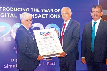 In quest to transform the payment system in the country, the Central Bank launched the 'Year of Digital Transactions-2020', a move that will set the ground for a transition from cash to digital transactions. Here, Central Bank, Deputy Governor H.A. Karunaratne presents a memento to Central Bank Governor W.D. Lakshman, flanked by a senior Central Bank official. Picture by Ranjith Asanka
