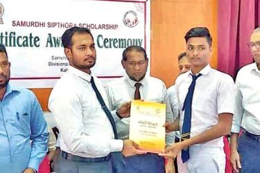 A student receives a scholarship from the Ampara District Samurdhi Director M.S.M. Sabraz at the event.