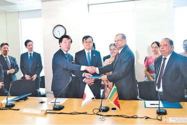 AASL Chairman G.A. Chandrasiri exchanges the agreement with Managing Executive Officer, Taisei Corporation Keiji Hirano, looked on by Ambassador of Japan to Sri Lanka Akira Sugiyama. Picture by Roshan Pitipane