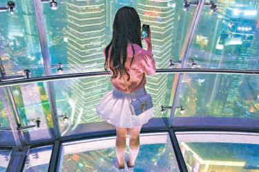 A young woman takes pictures of the city with her mobile phone, from the glass-floor observation platform, in the Oriental Pearl Tower, in the financial district of Shanghai.