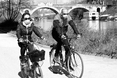 People wearing a protective mask ride their bicyclke along the river Tiber in Rome, as life goes on for Italians despite the shutting down of stores except for pharmacies and food shops in a desperate bid to halt the coronavirus. - AFP