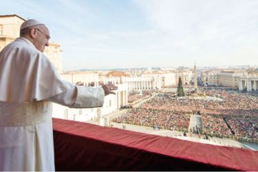 Pope Francis blessing the faithful from the central balcony of St. Peter's Basilica at the Vatican.