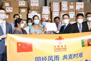 Health Minister Pavithra Wanniarachchi, Chinese Acting Ambassador Hu Wei and the members of the Chinese delegation pose for a photograph.
