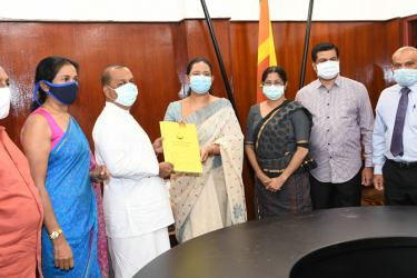 Power and Energy Minister Mahinda Amaraweera hands over the documents for two PCR machines to Health Minister Pavithra Wanniarachchi while officials look on.
