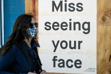 A woman in the US walks near a restaurant that alludes to face masks.  (AFP)