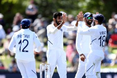 Jasprit Bumrah celebrates with his Indian teammates after taking a wicket against New Zealand.