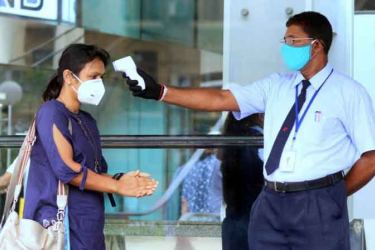 Security personnel check the temperature of an office worker in Colombo