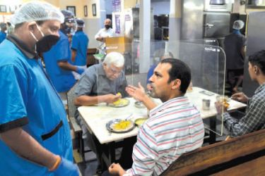 A customer talks to a waiter while eating his meal at a table divided with transparent panels as places of religious worship, hotels, restaurants and shopping malls are allowed to operate again after more than two months of lockdown imposed as a preventive measure against the COVID-19 coronavirus in Bangalore, India on Monday. - AFP