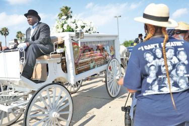 People watch as the horse drawn hearse containing the remains of George Floyd makes its way to the Houston Memorial Gardens cemetery on Tuesday, in Houston, Texas. - AFP