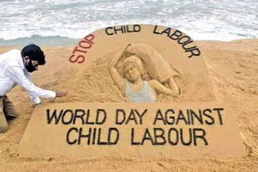 Artist Sudarsan Patnaik gives finishing touches to a sand sculpture with a message, Stop Child Labour, to mark World Day against Child Labour in Puri, India on Thursday. - PTI