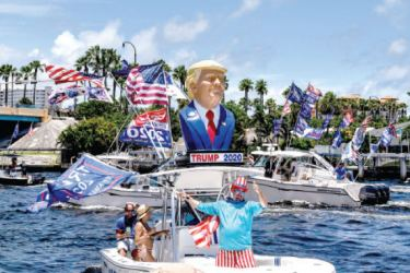 Supporters of US President Donald Trump wave flags as they participates in a boat rally to celebrate The President's birthday in Fort Lauderdale, Florida on Sunday. - AFP