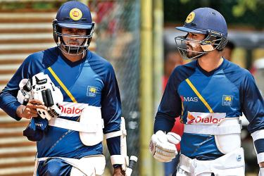 Angelo Mathews (L) speaks with teammate Dinesh Chandimal as they walks with their batting equipment during a practice session.