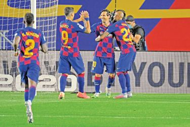 Barcelona's Argentine forward Lionel Messi (C) celebrates with teammates after scoring a penalty during the Spanish league football match FC Barcelona against CD Leganes at at the Camp Nou stadium in Barcelona on June 16. AFP