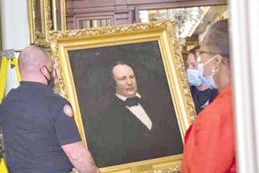 Clerk of the House Cheryl Johnson,(R), watches as Architect of the Capitol workers remove a portrait of James Orr of South Carolina that was hanging in the Speaker's Lobby on Capitol Hill in Washington on Thursday.