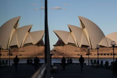 People stand near the Sydney Opera House as Australia reports first COVID-19 death in more than a month.