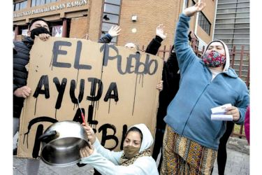 """Women bang pots next to a sign reading """"The people helps the people"""" to protest not getting aid during the coronavirus lockdown; the UN warns that 45 million people in Latin America and the Caribbean could fall into poverty because of the pandemic."""