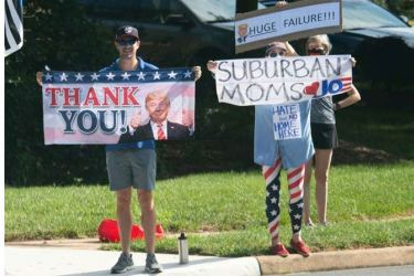 Supporters of Donald Trump and Joe Biden wave competing signs as the President's convoy arrived at a golf course in Sterling, Virginia in this August 23, 2020 file photo.
