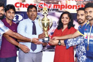 The Champion Dialog Axiata Chess team receiving the trophy from Chess Federation President Luxman Wijesuriya
