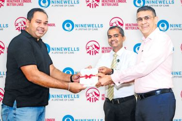AIA CEO Nikhil Advani and Ninewells Chief Operating Officer and Medical Director Dr. Vibash Wijeratne hand over the first complimentary AIA Life Cover to a new parent at Ninewells.