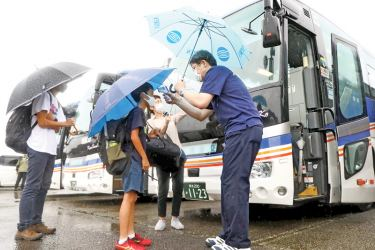 People undergo a temperature check before boarding a bus as an evacuation advice is issued due to the approach of typhoon Haishen in Hitoyoshi, Kumamoto Prefecture on September 6, 2020. - Typhoon Haishen headed toward southern Japan on September 6, with officials warning of record rainfall and winds strong enough to snap power poles and flip vehicles.  AFP
