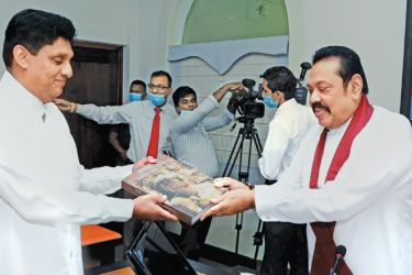 Prime Minister Mahinda Rajapaksa presents a book on the 2600th Sambuddhawa Jayanthi to Opposition Leader Sajith Premadasa at Temple Trees yesterday. Ven. Dr. Diviyagaha Yasassi Thera was also present. Picture courtesy Prime Minister's Media Division
