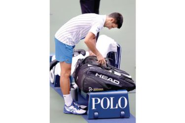 Novak Djokovic packs his bag to leave the court after being defaulted due to inadvertently striking a lineswoman with a ball hit in frustration during his Men's Singles fourth round match against Pablo Carreno Busta of Spain on Day Seven of the 2020 US Open on Sunday. AFP