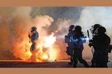Oregon Police wearing anti-riot gear march towards protesters through tear gas smoke during the 100th day and night of protests against racism and police brutality in Portland, Oregon in this September 5, 2020 file photo. - AFP