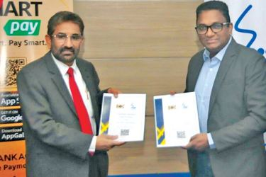 General Manager of BOC, Sugath Gunasekara (left) and Chief Executive Officer of SLT, Kiththi Perera exchanging the Agreement between SLT and Bank of Ceylon.