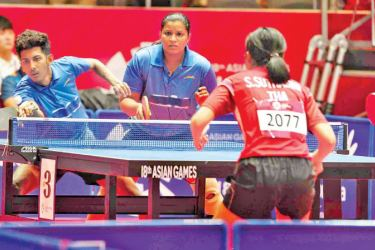 Sri Lankan pair of  Ishara Madurangi and Imesh Rangasinghe in their mixed doubles game against Thailand at the 18th Asian Games in Jakarta.